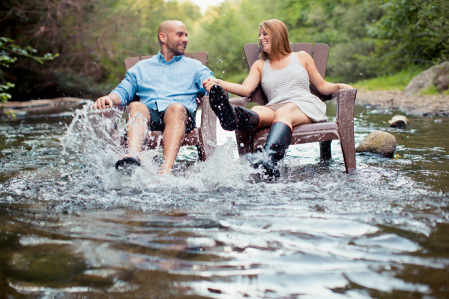 Couple splashing water up while they sit in adirandak in the river