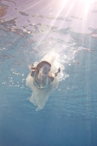 Bride swimming in the water in BHLDN wedding gown