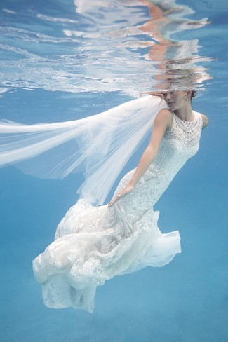 Bride wearing tulle veil and mermaid wedding gown swimming in the water