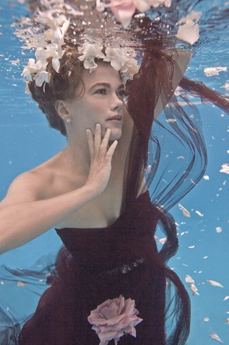 Bridesmaid swimming under water wearing dark purple BHLDN gown and floral crown