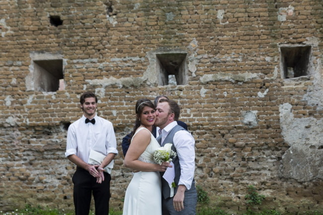 Groom kissing brides cheek during intimate outdoor ceremony at Aventine Hill