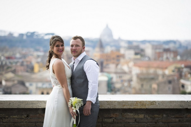 Bride and groom standing on hill over looking Rome