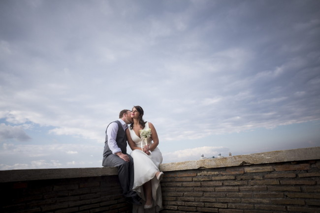 Groom kissing bride while sitting on marble terrace overlooking the city of Rome