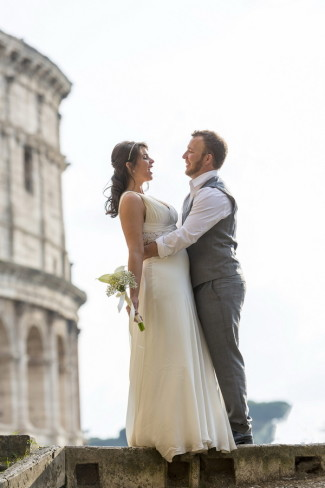 Groom holding brides waist while they stand on a wall in front of the Roman Colosseum