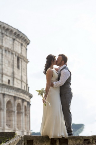 Bride and groom kissing on wall with Roman Colosseum in background
