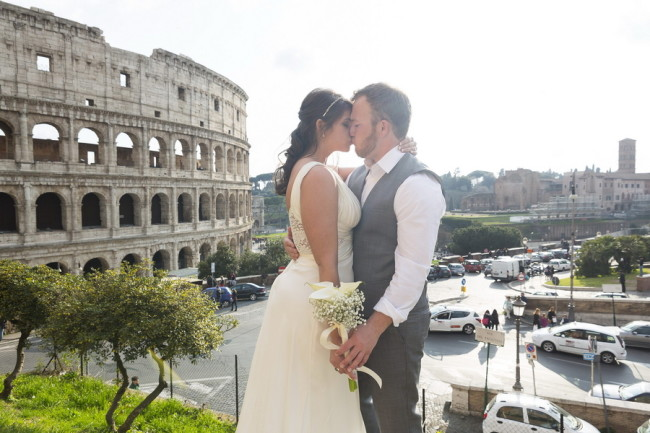Bride and groom kissing in front of the Roman Colosseum
