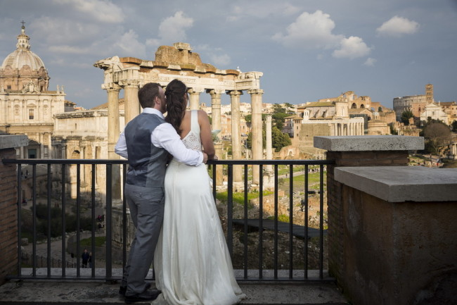 Bride and groom facing away from camera looking at Roman Forum
