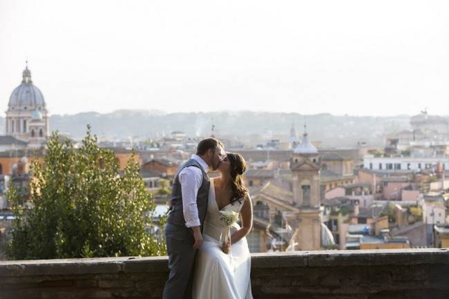 Bride and groom kissing on marble terrace overlooking the city of Rome