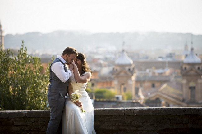 Groom kissing his brides hand while she sits on marble terrace overlooking the city of Rome
