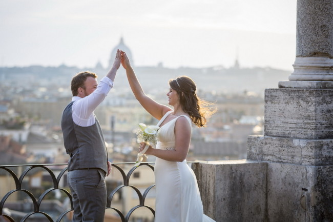 Bride and groom dancing on terrace over looking Rome