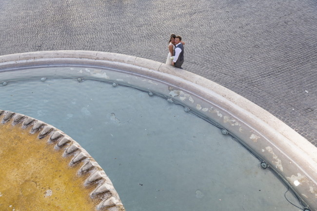 Bride and groom standing in front of fountain in Piazza del Popolo