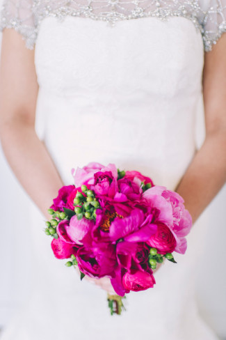 Bride carrying bright pink with green foliage bridal bouquet