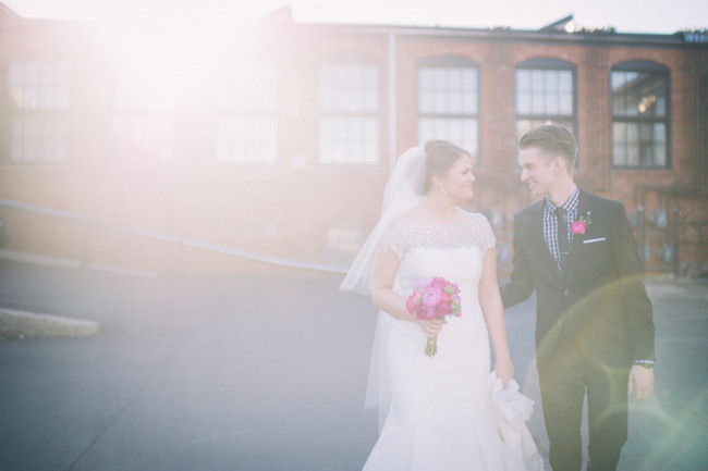 Bride and groom standing outside with light shining through capture by Sarah katherine davis