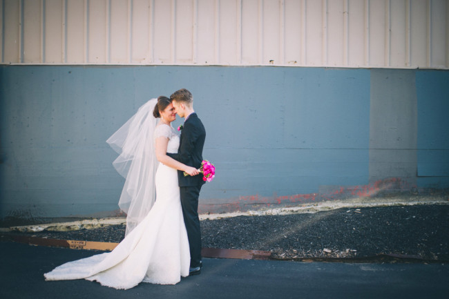 Bride wearing a floor length veil with blush embracing her groom wearing black suit