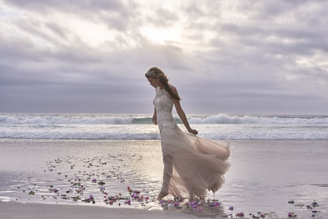 Bride walking along shore line in a BHLDN Tulle dress