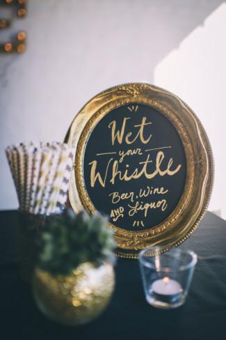 Gold frame with chalkboard sign inside for bar sign at wedding reception