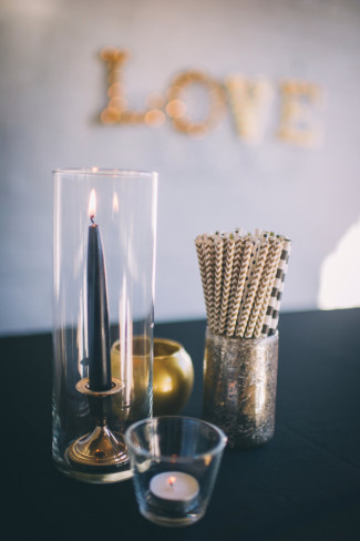 Black table cloth with gold paper straws, gold tea light holder and black candle for wedding decor