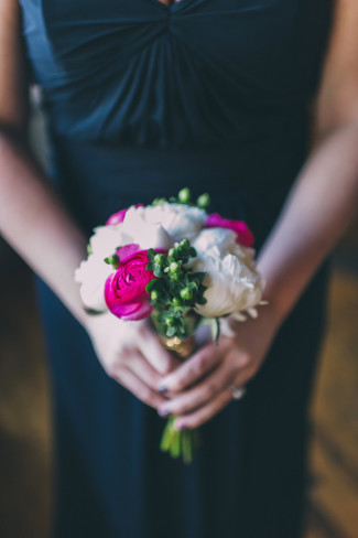 Bridesmaid wearing black dress carrying a white and bright pink floral bouquet