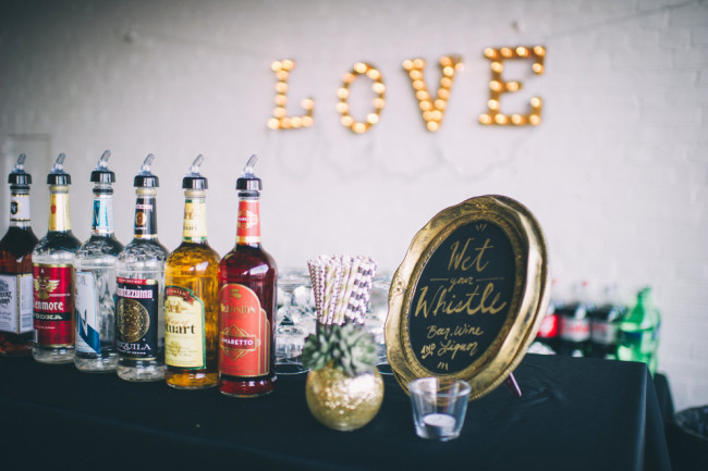"Wedding reception bar with gold chalkboard frame with ""wet your whistle"" and an illuminated Love sign"