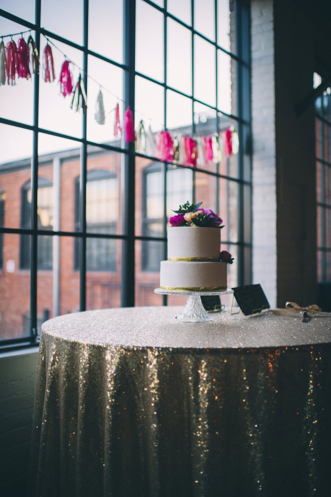 2-tier wedding cake on a cocktail table that has gold sequin table cloth