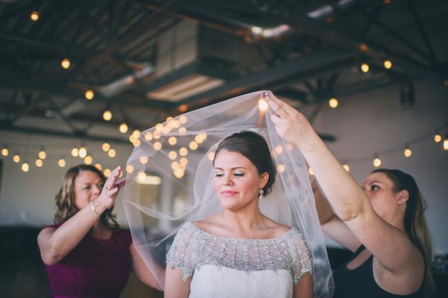 Bridesmaids putting brides blusher over brides head