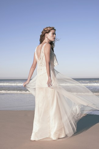 Bride standing on the beach wearing a BHLDN Wedding gown with tulle over lay