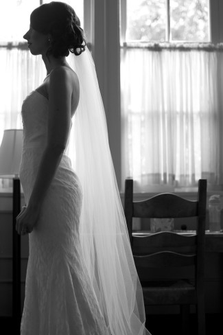 Bride standing side ways wearing a floor length veil