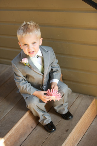 Ring bearer sitting on the steps wearing a grey suit and black shoes