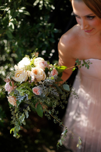 Bridesmaid wearing blush pink gown from bhldn holding floral bouquet