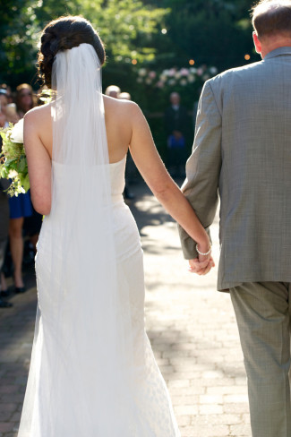 Bride wearing floor length veil walking down aisle holding hands with her father