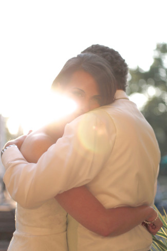 Bride and groom embracing each other with sun shining through capture by Sherri Diteman Kaven