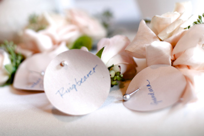 boutonnieres with paper and pins with the receivers name written on the paper