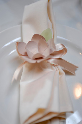 Wedding reception cloth napkin with paper flower tied around it