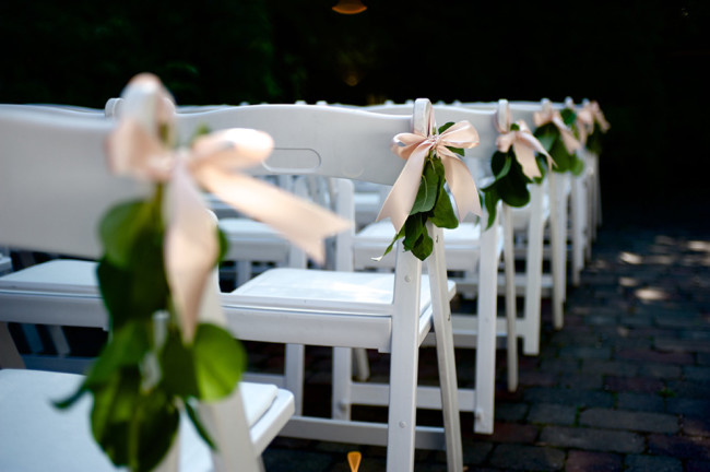 Ceremony chair decor with green leafs and pink bows