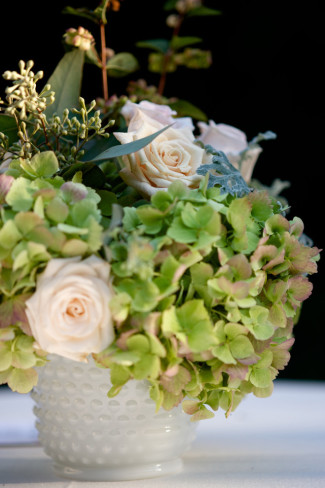 green hydrangeas and blush pink roses in milk glass vase