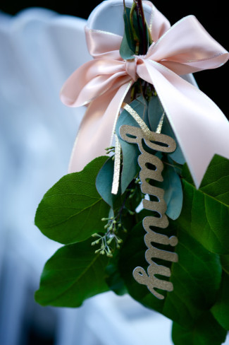 "Ceremony chair decor with green leafs, pink bows and gold ""family"" cut out hanging"