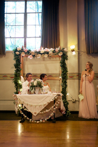 Bride and groom sitting at head table with arch way of paper flowers