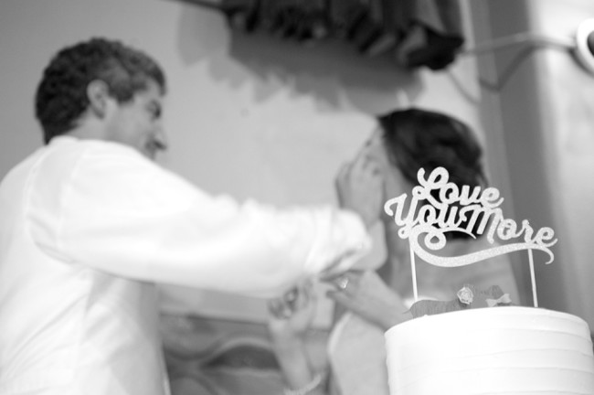 "Groom feeding bride cake with a small wedding cake to the side with ""Love you more"" cake topper"