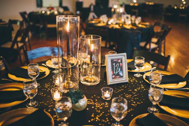 Wedding reception place setting with black table cloth and napkins on gold charger