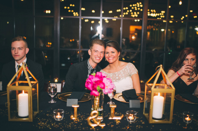 Bride and groom pose at head table with black table cloth and gold lanterns
