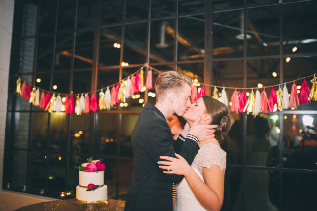 Bride and groom kissing after cake cutting ceremony with pink and gold tassels hanging on the wall