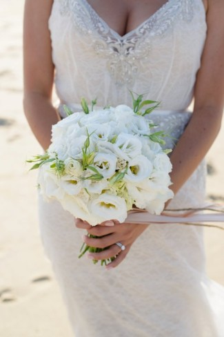 Bride carrying white bridal bouquet created by bells and whistles