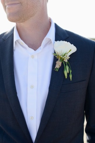 Groom wearing white boutonniere, black suit and white shirt