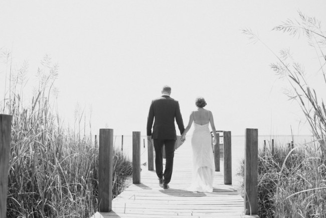 Black and white photo of bride and groom holding hands walking down pier at sanderling resort
