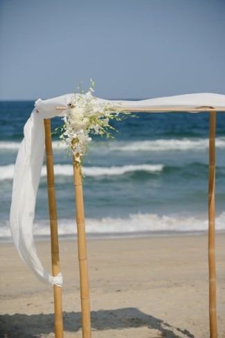 Bamboo beach ceremony altar with white flowing material
