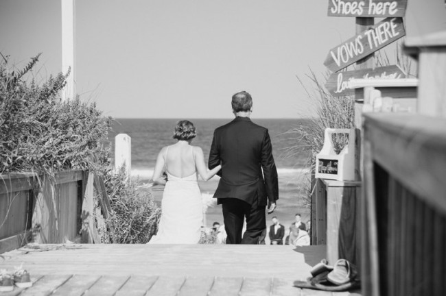 Black and white photo of father walking bride down aisle at Sanderling Resort beach wedding