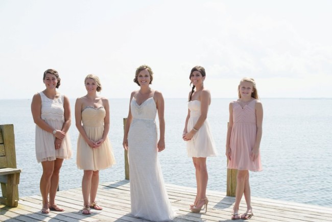 Bride standing on pier in front of the ocean with bridesmaids wearing mismatched yellow and pink dresses