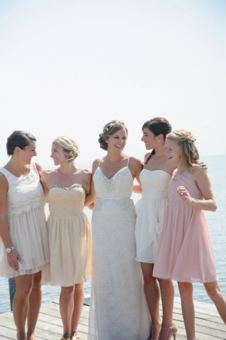 Bride standing with bridesmaids in mistmatched bring and yellow dresses