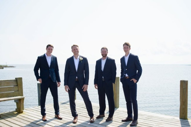 groom standing with groomsmen in black suits on pier at Sanderling Resort