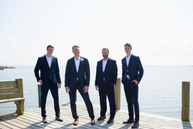 groom standing with groomsmen in black suits on pier at Sanderling Resort